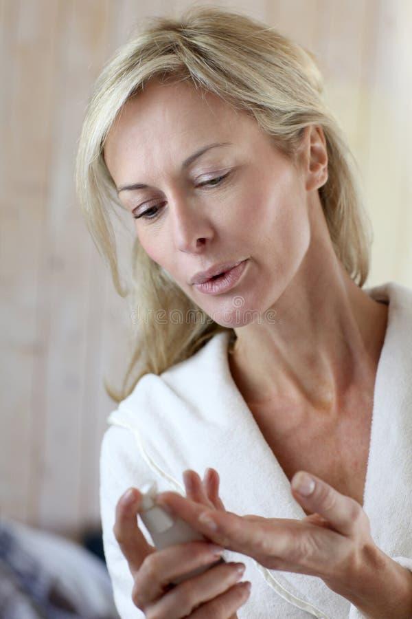 Attraktiv medelålders kvinna som sätter kräm på hennes framsida arkivbild