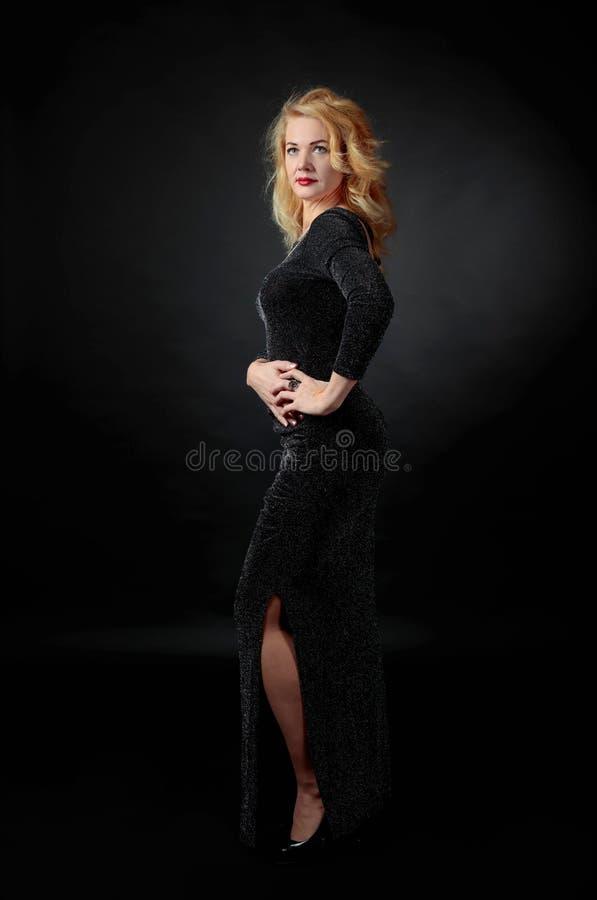 Attraktiv mellersta ålderkvinna i svart aftonklänning arkivfoto