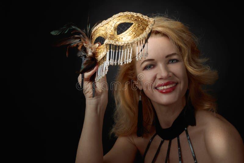 Attraktiv mellersta ålderkvinna i svart aftonklänning med den guld- karnevalmaskeringen arkivfoto