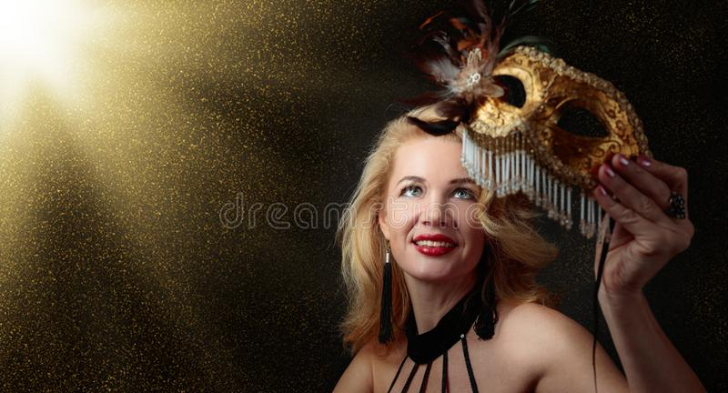 Attraktiv mellersta ålderkvinna med den guld- karnevalmaskeringen arkivfoton