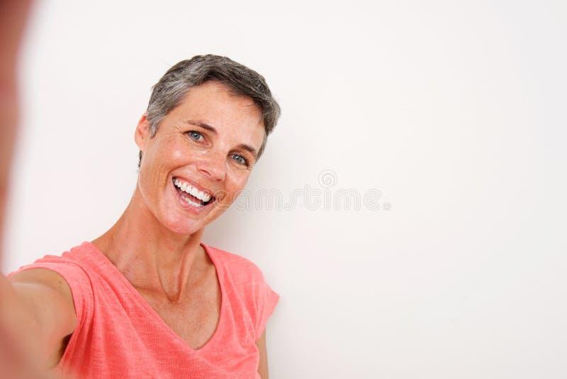 Attraktiv mellersta ålderkvinna som ler och tar selfie royaltyfri bild