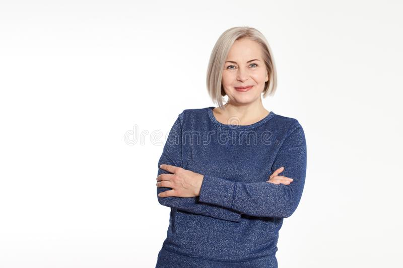 Attraktiv mellersta åldrig kvinna med vikta armar på vit bakgrund arkivfoton