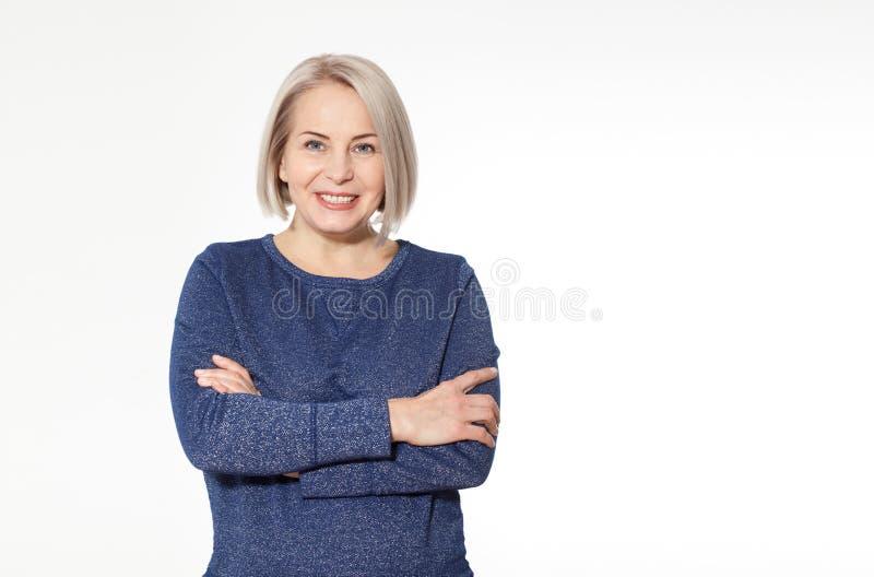 Attraktiv mellersta åldrig kvinna med vikta armar på vit bakgrund arkivfoto