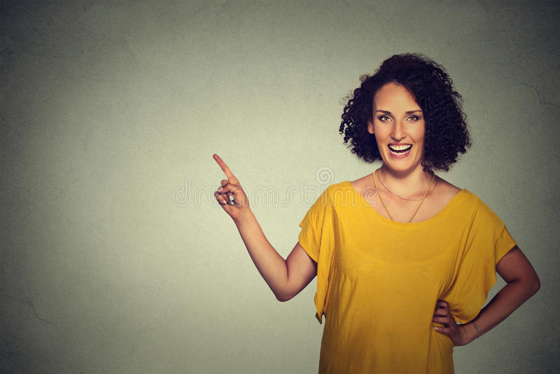 Attraktiv mitt åldras kvinna som pekar på bakgrund för mellanrumsgrå färgvägg royaltyfri fotografi