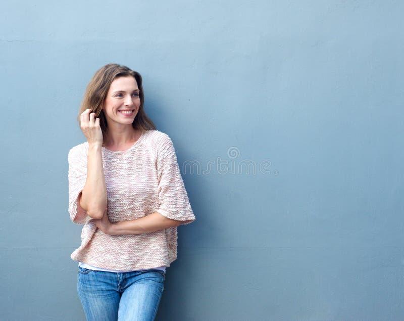 Attraktiv mitt- vuxen kvinna som ler med handen i hår arkivfoton