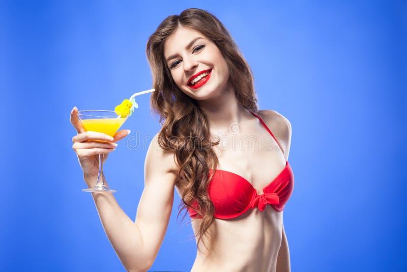 Attraktiv modell i röd bikinibehå med den exotiska coctailen och sugrör royaltyfria foton