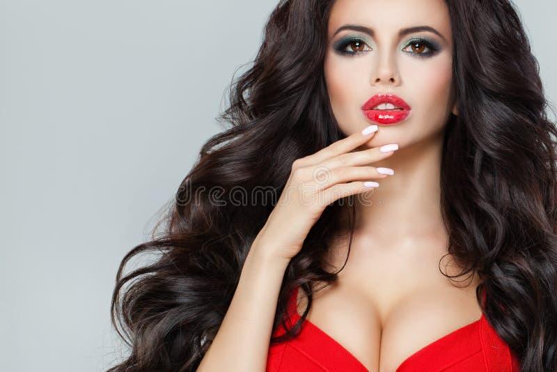 Attraktiv modell med mörkt lockigt hår, röd kantmakeup royaltyfri bild