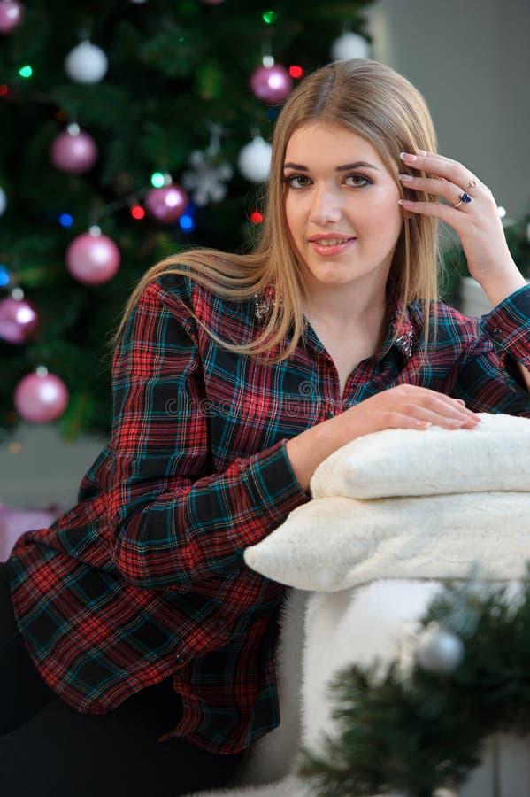 Attraktiv modell som ligger nära en julgran lycklig kvinna Nytt Y arkivfoto