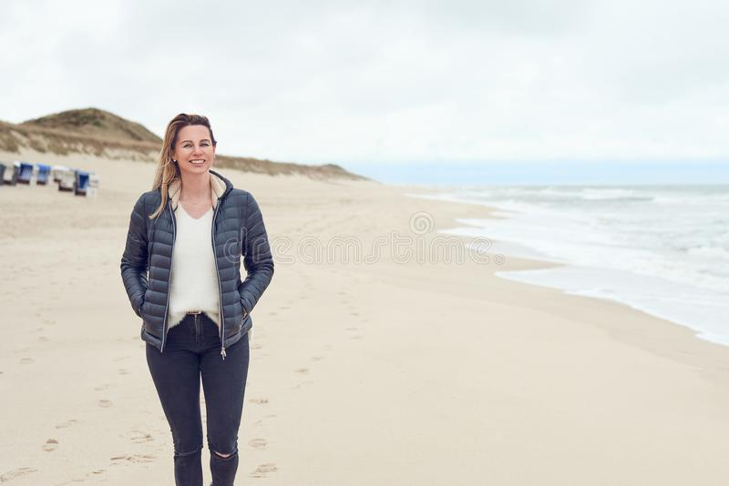 Attraktiv moderiktig kvinna som går på en öde sandig strand royaltyfria foton