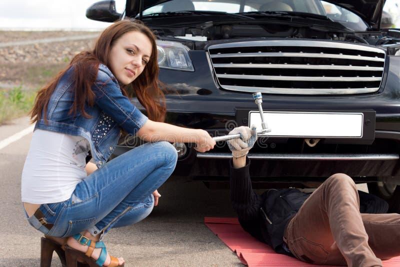 Attraktiv moderiktig ung kvinna som fixar hennes bil fotografering för bildbyråer