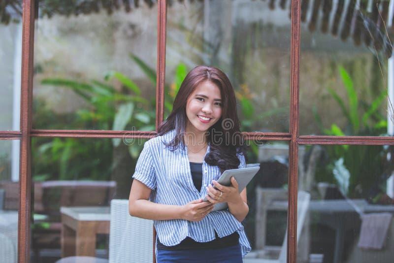 Attraktiv modern kvinna som ler med minnestavlan royaltyfria bilder
