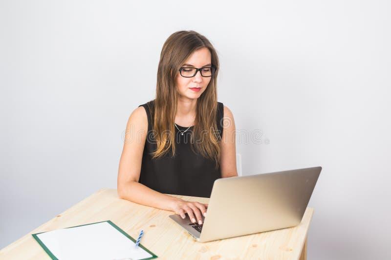 Attraktiv mogen affärskvinna som arbetar på bärbara datorn i hennes arbetsstation royaltyfria foton