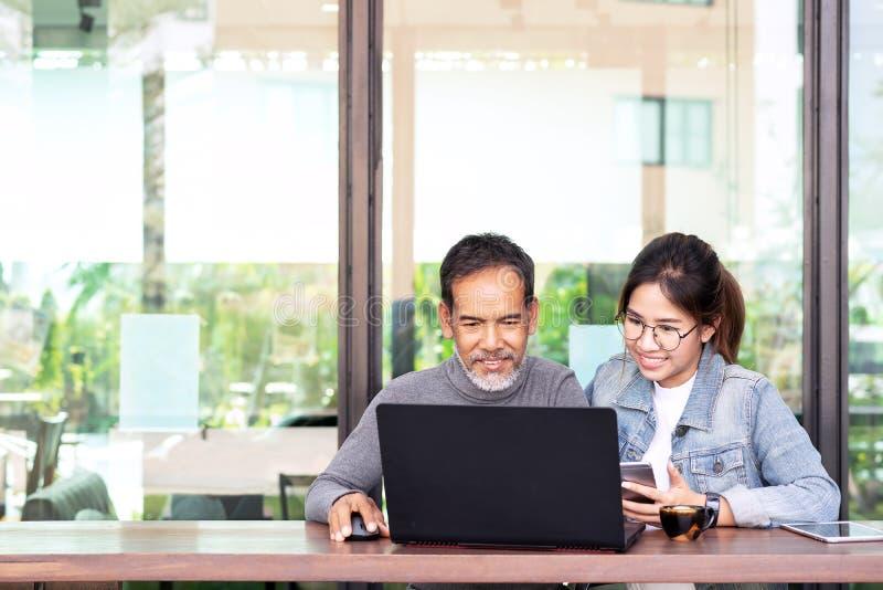 Attraktiv mogen asiatisk man med det vita stilfulla korta sk?gget som ser b?rbar datordatoren med den ton?rs- kvinnan f?r ?gonexp royaltyfria bilder