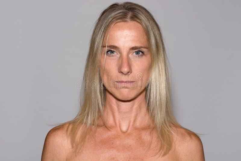 Attraktiv mogen blond kvinna med kala skuldror arkivbild