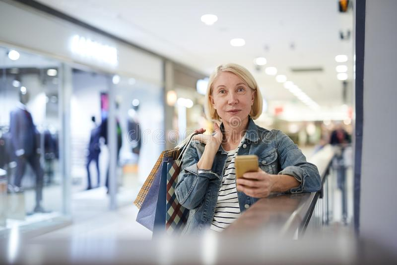 Attraktiv mogen dam som överför fotomeddelandet till vännen under shopping arkivbild