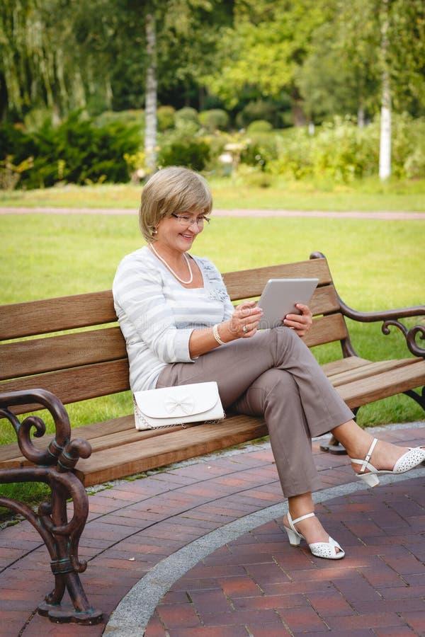 Attraktiv mogen kvinna som använder den digitala minnestavlan i en parkera arkivbilder