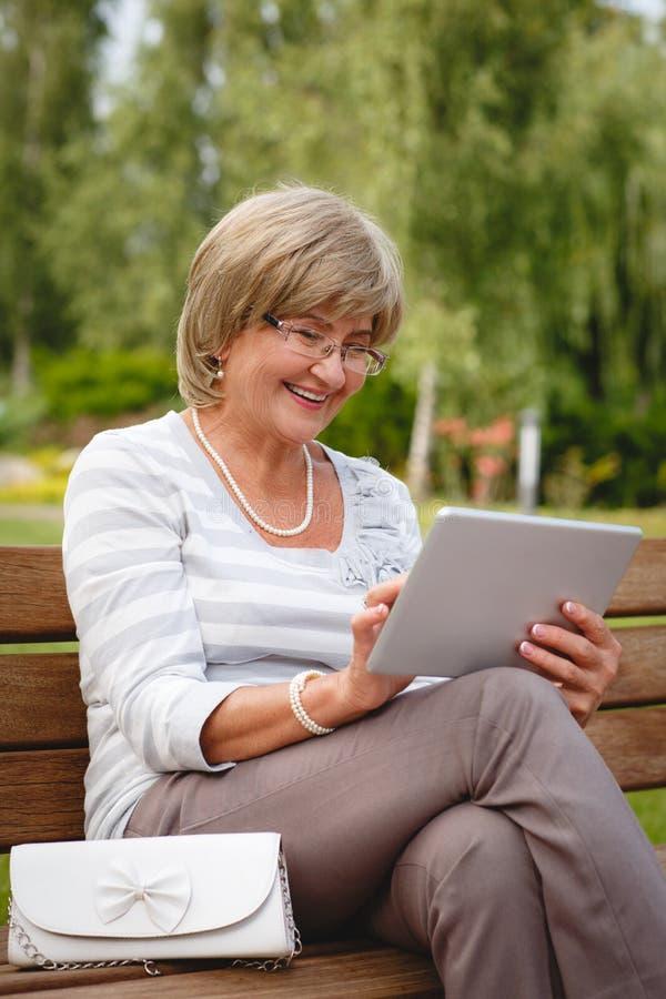 Attraktiv mogen kvinna som använder den digitala minnestavlan i en parkera royaltyfri fotografi