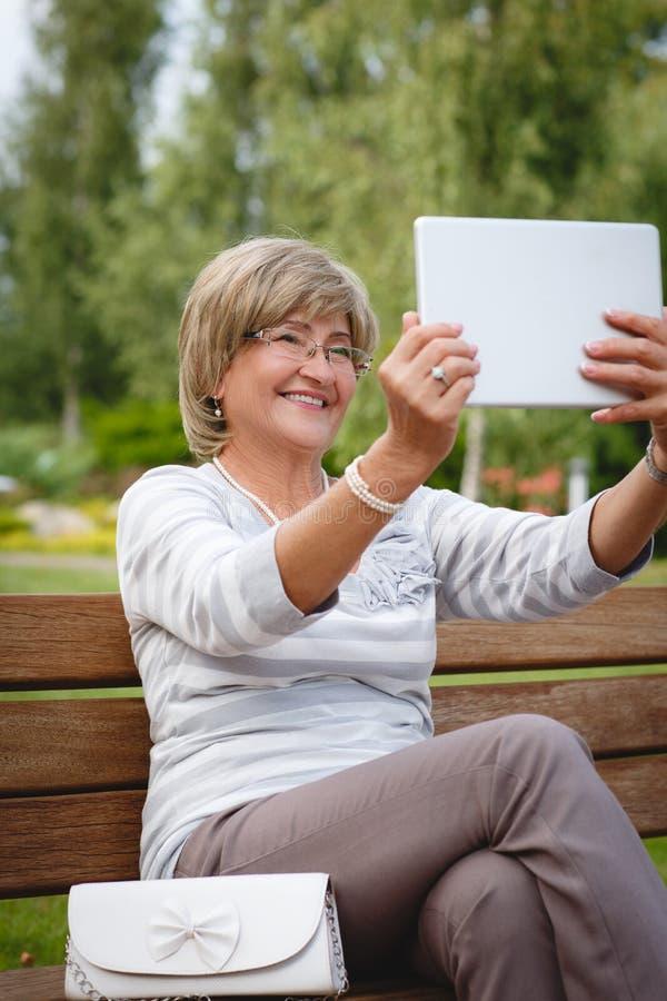 Attraktiv mogen kvinna som använder den digitala minnestavlan i en parkera royaltyfri bild