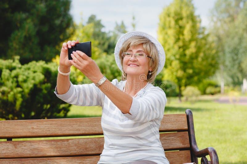 Attraktiv mogen kvinna som använder smartphonen i en parkera royaltyfri foto