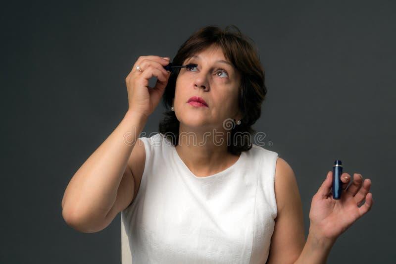 Attraktiv mogen kvinna som applicerar mascara royaltyfri bild