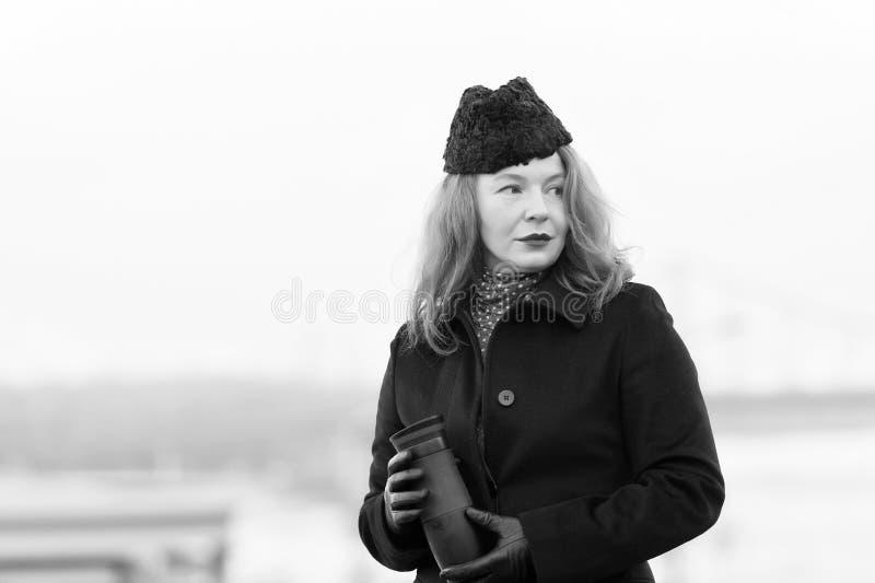 Attraktiv mogen kvinna som rymmer en termosflaska arkivfoto
