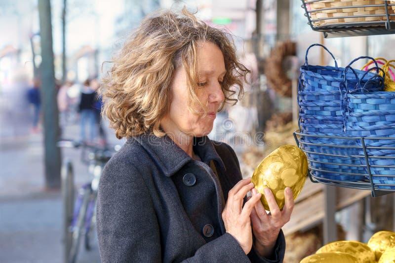 Attraktiv mogen kvinna som ser ett påskägg royaltyfria bilder