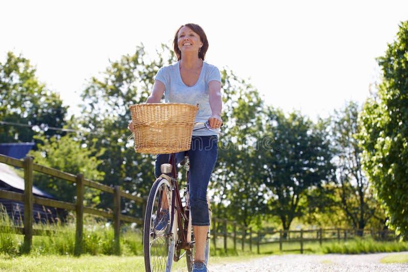 Attraktiv mogen kvinnaridningcykel längs landsgränd royaltyfria foton