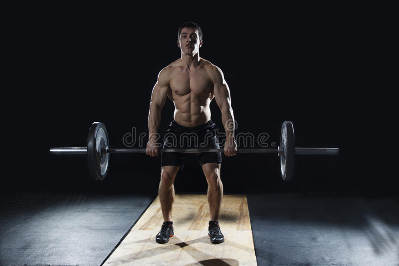 Attraktiv muskulös kroppsbyggare som gör deadlifts i modern fitne fotografering för bildbyråer
