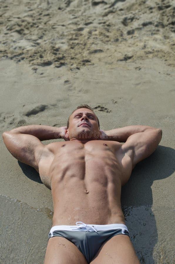 Attraktiv muskulös ung man som vilar på stranden, stor copyspace