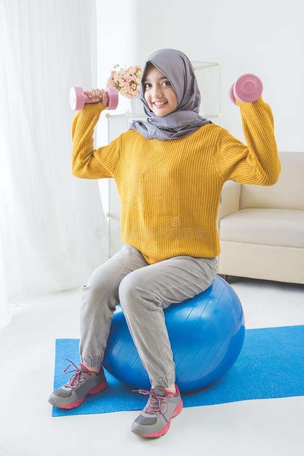 Attraktiv muslimkvinnakondition genom att använda hanteln arkivbilder