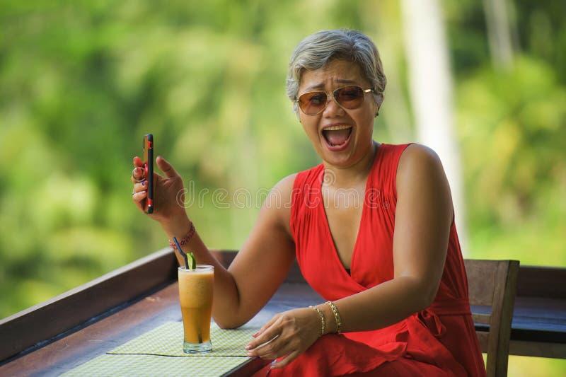 Attraktiv och avkopplad 40-tal eller asiatisk kvinna för 50-tal med grått hår och den stilfulla röda klänningen genom att använda arkivfoto