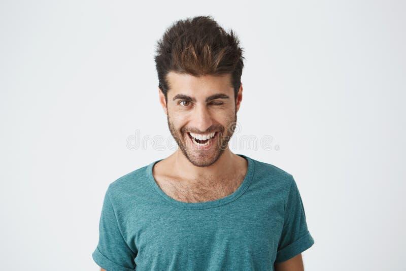 Attraktiv och gladlynt ung man med skägget och stilfull frisyr som bär den blåa t-skjortan som blinkar hans ögon med nöje fotografering för bildbyråer