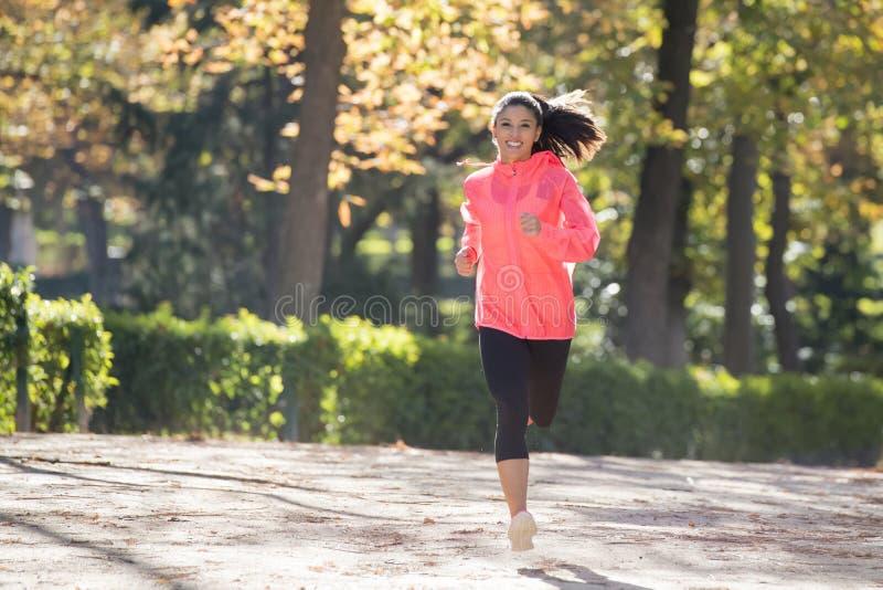 Attraktiv och lycklig löparekvinna i höstsportswearen som kör a fotografering för bildbyråer