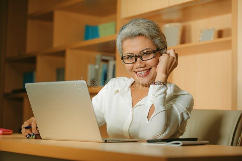 Attraktiv och lycklig lyckad mogen asiatisk kvinna som arbetar kopplat av p? att le f?r skrivbord f?r b?rbar datordator som ?r s? arkivbild