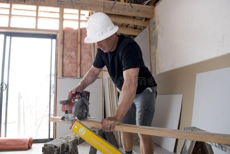 Attraktiv och säker konstruktörsnickare eller byggmästareman i den skyddande hjälmen som arbetar lyckligt bitande trä på industri royaltyfri foto