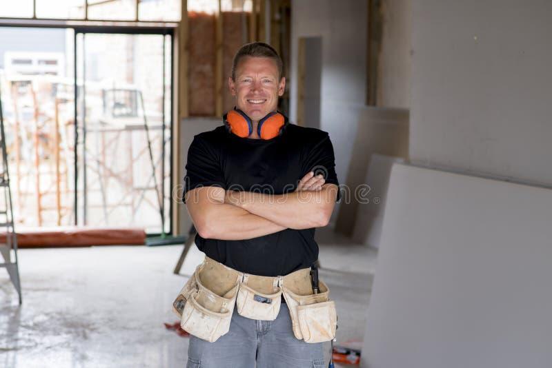 Attraktiv och säker konstruktörsnickare eller byggmästareman med att arbeta för kugghjul för öraskydd som är lyckligt på industri arkivbild