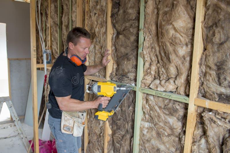 Attraktiv och säker konstruktörsnickare eller funktionsdugligt trä för byggmästareman med den elektriska drillborren på den indus arkivbild