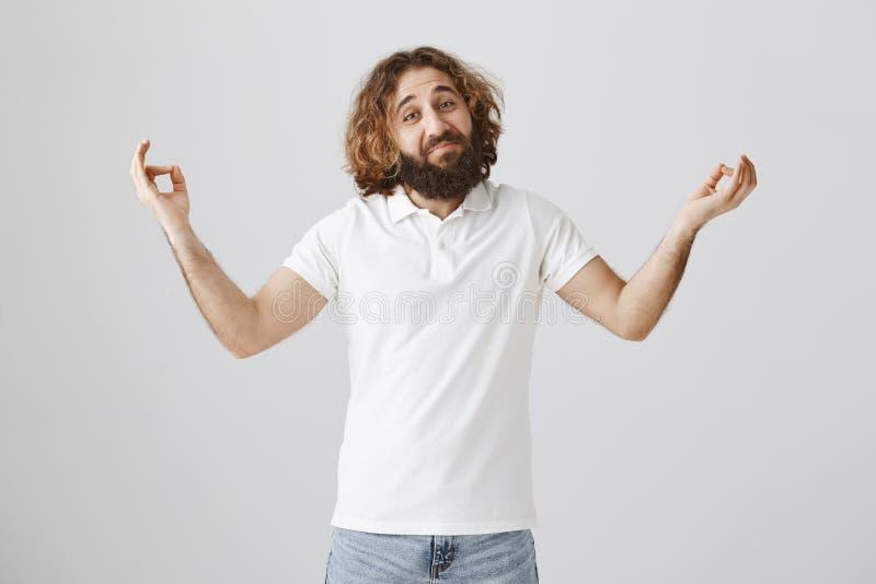 Attraktiv och vänlig östlig grabb med skägget och lockigt hår som försöker den nya meditationmetoden som står med spridninghänder arkivbilder