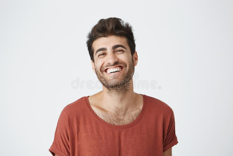 Attraktiv orakad ung mörkhyad man i röd tshirt som ler brett att skratta på den roliga bilden på internet positivt royaltyfri foto