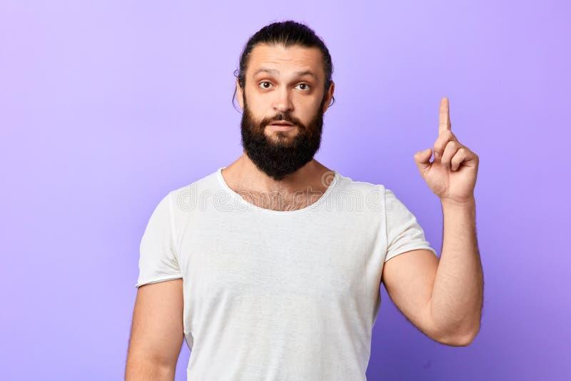 Attraktiv orakad ung man i den vita t-skjortan som pekar upp arkivfoto