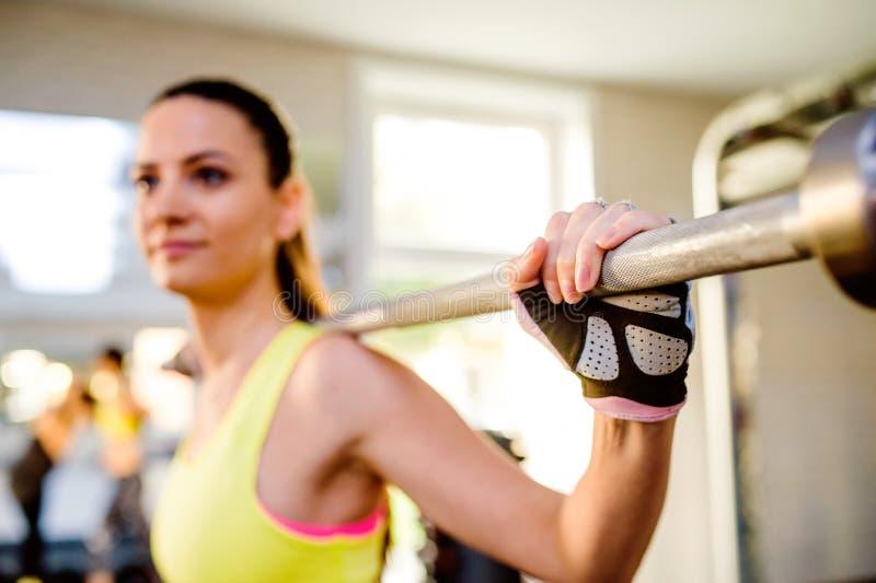 Attraktiv passformkvinna i idrottshall som övar med vikter arkivfoton