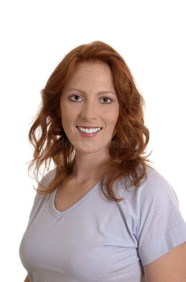 Attraktiv röd haired kvinna som ler, stående royaltyfria foton