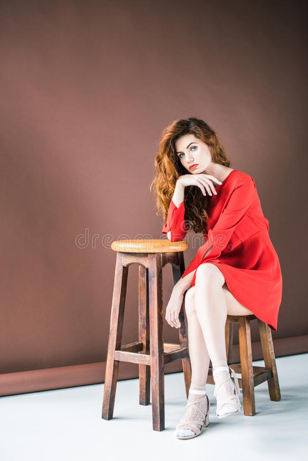 Attraktiv rödhårig mankvinna som sitter på stol royaltyfri bild