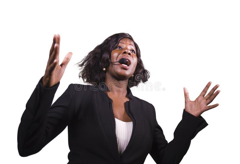 Attraktiv säker affärskvinna med mikrofonhörlurar med mikrofon som in talar till åhörare i salong på det företags händelseseminar arkivbild