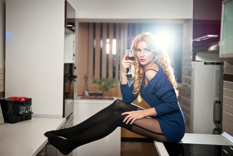 Attraktiv sexig blond kvinnlig med den ljusa blåa blusen och svarta strumpor som poserar att le rymma ett exponeringsglas med rött royaltyfria bilder