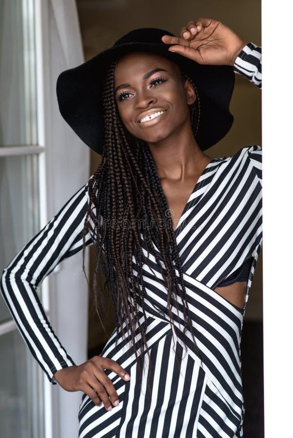 Attraktiv sexig flicka med mörk skinande hud som poserar för kameraanseende av fönstret som trycker på hennes hatt royaltyfri foto