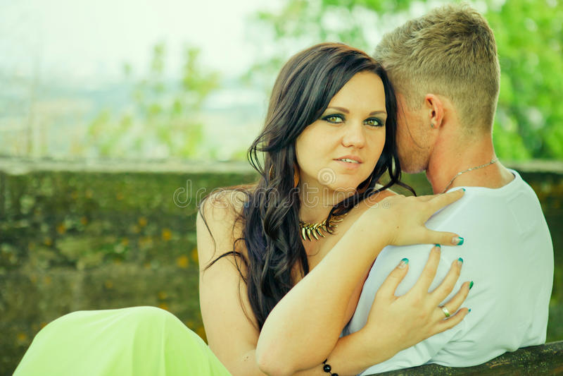 Attraktiv sitzen der Kerl mit dem Mädchen und umfassen auf einer Bank lizenzfreies stockfoto