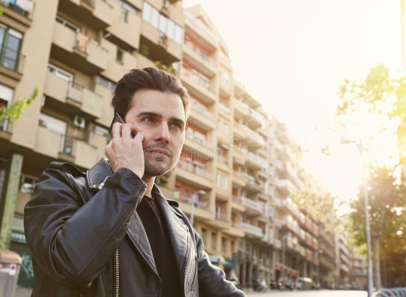 Attraktiv skäggig man som använder en smart telefon i hans hand på den soliga stadsgatan fotografering för bildbyråer