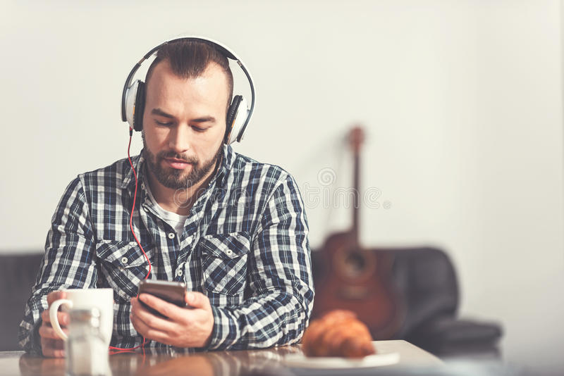 Attraktiv skäggig man som lyssnar till musik arkivfoton