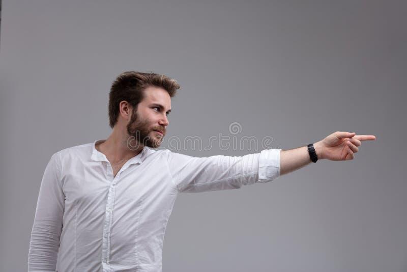 Attraktiv skäggig man som pekar till sidan arkivfoto
